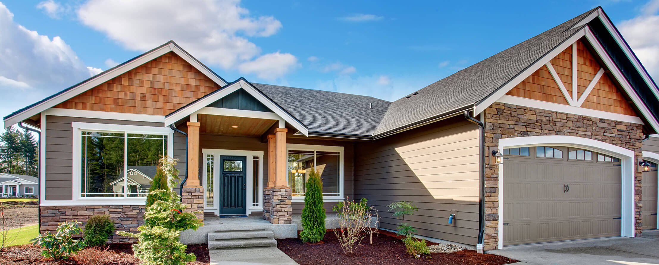 Newly built home with cedar shakes, vinyl siding, and stone facade and professional landscaped yard