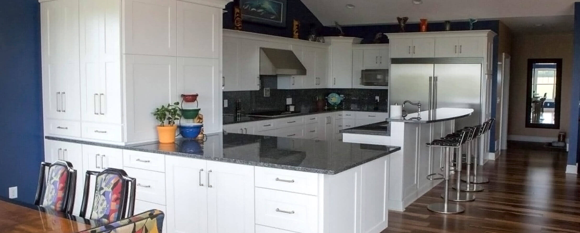 Kitchen with white cabinets, stainless steel appliances, wood floors, and navy blue walls