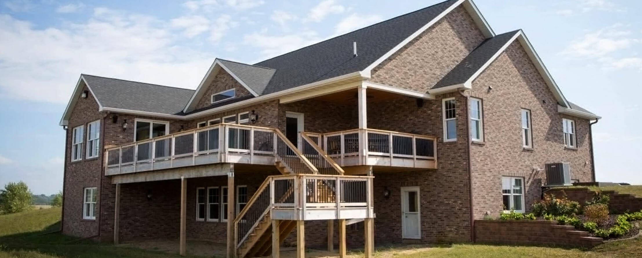 Large newly constrution brick home with an oversized deck